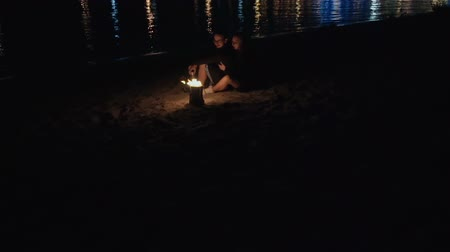 couple sitting on the beach near a campfire