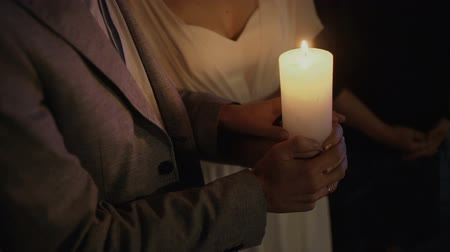 Bride and groom lighting up a candle as a symbol of love