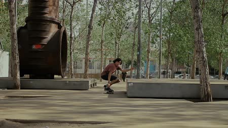 riskli : Skateboarder doing a jumping trick at skateboard park Stok Video