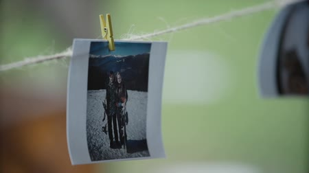 csatolt : Girl looks at the photo where two lovers are depicted.The photo is attached with clothespins to the string. Stock mozgókép