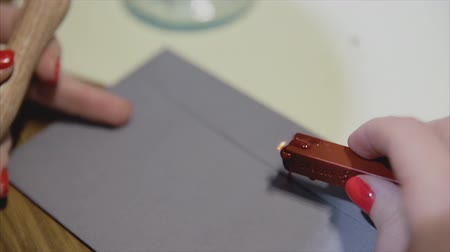 belgeleme : Girl put a seal with a sealing wax.Red wax seal or signet on lilac envelope.