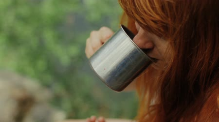 cilindro : Girl holds a cup of hot tea.Girl drinks tea in the forest.