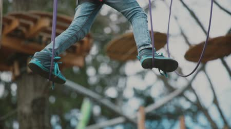 hawser : young boy passing the cable route high among trees, extreme sport in adventure park Stock Footage
