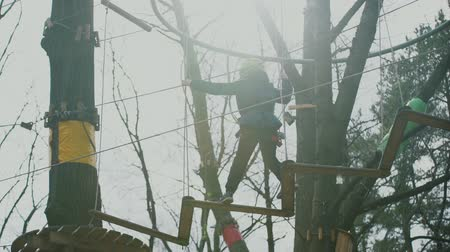 kamp : young boy passing the cable route high among trees, extreme sport in adventure park Stok Video