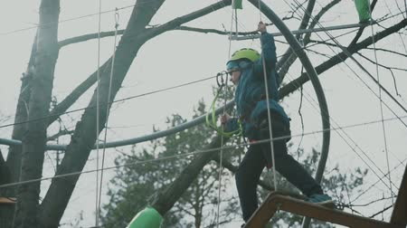 harcerz : young boy passing the cable route high among trees, extreme sport in adventure park Wideo