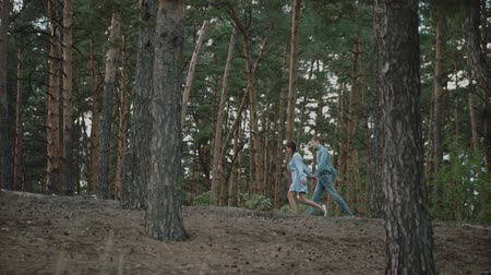 芝 : A young attractive couple walking through the forest with their happy dog.Couple in love play with the dog shiba in pine forest .Sunny weather.Slow motion.