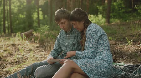 souvenirs : Couple sitting in picnic in the sunset forest. Family looking at their photo album sitting in the park. Happy couple with photo album.A young attractive couple walking through the forest with their happy dog. Stock Footage