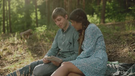 memories photos : Couple sitting in picnic in the sunset forest. Family looking at their photo album sitting in the park. Happy couple with photo album.A young attractive couple walking through the forest with their happy dog. Stock Footage