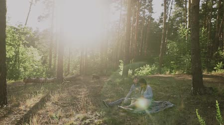 cam : Couple sitting in picnic in the sunset forest. Family looking at their photo album sitting in the park. Happy couple with photo album.A young attractive couple walking through the forest with their happy dog. Stok Video