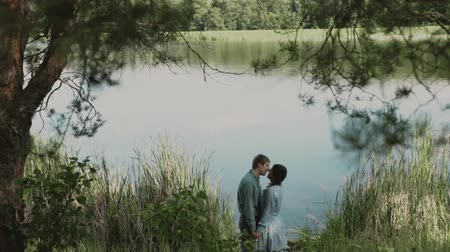 fresh air : A loving couple is standing by the lake and looking at each other.Smiling couple.A young attractive couple walking through the forest with their happy dog.Slow motion.