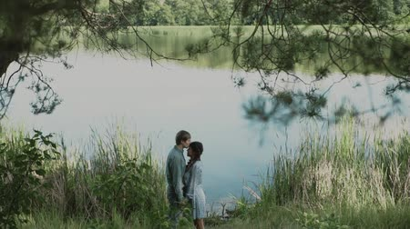 芝 : A loving couple is standing by the lake and looking at each other.Smiling couple.A young attractive couple walking through the forest with their happy dog.Slow motion.