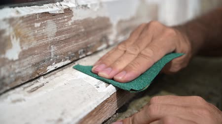протирать : Slow motion shot of a mans hand sanding a worn window sill