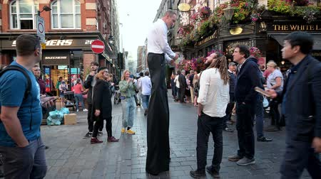 gimmick : LONDON - SEPTEMBER 13, 2019: Man on stilts in the crowded streets of Covent Garden promoting local businesses
