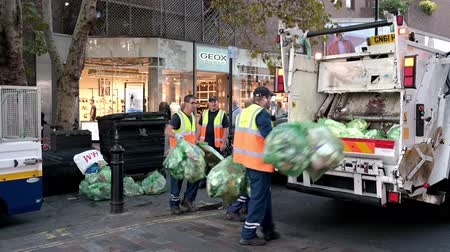 covent : LONDON - SEPTEMBER 13, 2019: Street cleaners loading bin bags into the back of a garbage truck on the streets around Covent Garden