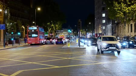 двойной : LONDON - SEPTEMBER 10, 2019: Slow zoom in on traffic crossing a busy intersection at Kings Cross at night. Taken from traffic island in the middle of the road. Стоковые видеозаписи