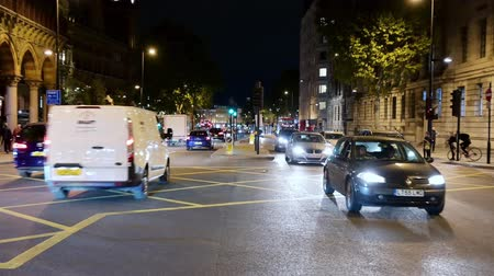 station de bus : Londres - 10 septembre 2019: lent zoom arrière du trafic traversant une intersection achalandée à King's Cross la nuit. Pris de l'île de la circulation au milieu de la route.