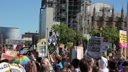 big ben : LONDON - SEPTEMBER 20, 2019: Protest placards held high in front of The Houses of Parliament before an Extinction Rebellion march