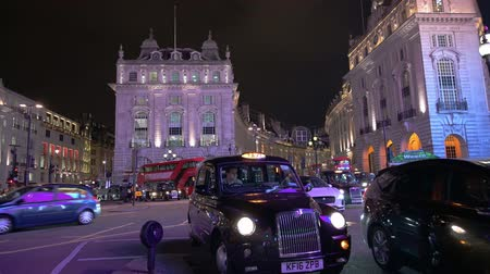 london cab : LONDON - OCTOBER 23, 2019: London black cabs and double decker buses lit by glow from famous digital billboards at Piccadilly Circus at night