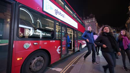 exiting : LONDON - OCTOBER 23, 2019: People getting off a London double decker bus at the side of the road in Piccadilly Circus at night Stock Footage