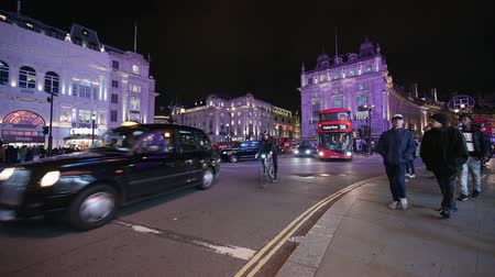 london cab : LONDON - OCTOBER 23, 2019: London double decker bus passing crowds of people in Piccadilly Circus at night