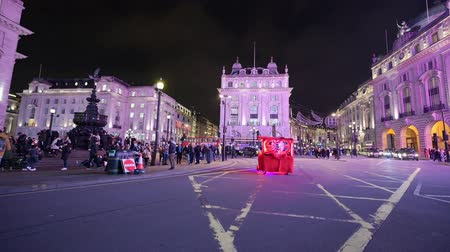 amor : LONDON - OCTOBER 23, 2019: A glowing red rickshaw crosses Piccadilly Circus at night in the light from the famous digital billboards