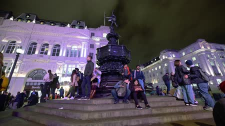 london cab : LONDON - OCTOBER 23, 2019: Tourists on the steps beneath the statue of Eros in Piccadilly Circus at night lit by the glow from the famous digital billboards Stock Footage