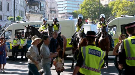 animais em extinção : LONDON - SEPTEMBER 20, 2019: Mounted police and police vans at an Extinction Rebellion march at Trafalgar Square, London