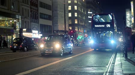 london cab : LONDON - OCTOBER 23, 2019: Buses and taxis on The Strand at night