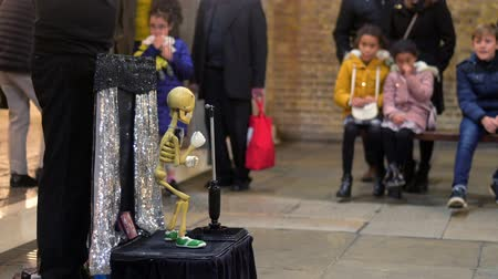 hallows : LONDON - OCTOBER 23, 2019: Street performers skeleton puppet at Covent Garden with kids watching in the background Stock Footage