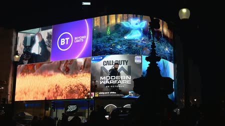 lots of : LONDON - OCTOBER 23, 2019: Eros silhouetted against the advertisements on the digital billboard at Piccadilly Circus at night Stock Footage
