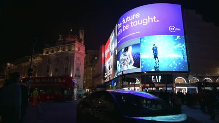 点滅する : LONDON - OCTOBER 23, 2019: People and traffic in front of the famous digital billboards of Piccadilly Circus at night
