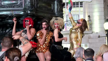 amor : LONDON - SEPTEMBER 14, 2019: Cross dressers posing for photographs at the base of the Eros statue in Piccadilliy Circus at night. Flamboyantly dressed and with beards, they pose for the camera.