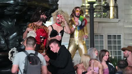 amor : LONDON - SEPTEMBER 14, 2019: Cross dressers gathered at the base of the Eros statue in Piccadilliy Circus at night.