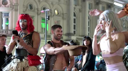 amor : LONDON - SEPTEMBER 14, 2019: A group of cross dressers singing at the base of the Eros statue in Piccadilliy Circus at night. They encourage the crowds of tourists to join them in singing Happy Birthday to one of their group.