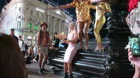 ориентация : LONDON - SEPTEMBER 14, 2019: A drunken cross dresser in high heels falls down while trying to jump down the steps at the base of the Eros statue in Piccadilly Circus