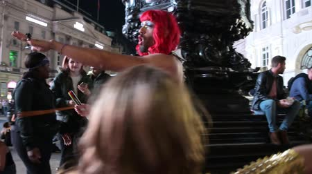 amor : LONDON - SEPTEMBER 14, 2019: A group of transvestites entertaining the crowds of tourists in Piccadilly Circus at night. Lit by the glow from the famous digital billboard.