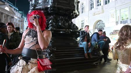 minoria : LONDON - SEPTEMBER 14, 2019: Cross dressers drinking and partying at Piccadilly Circus at night in front of the statue of Eros