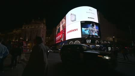 amor : LONDON - SEPTEMBER 14, 2019: Pedestrians and traffic passing in front of the famous digital screens in Piccadilly Circus at night
