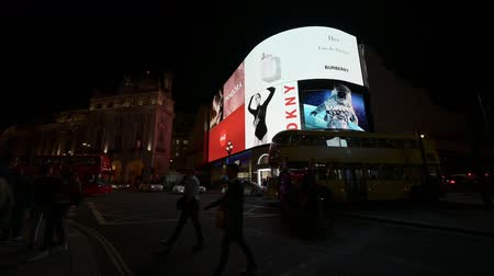 cupido : LONDON - SEPTEMBER 14, 2019: A London Double Decker bus crosses Piccadilly Circus in front of the famous digital screens at night. People cross the road in front of a rickshaw. Vídeos