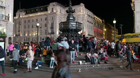 amor : LONDON - SEPTEMBER 14, 2019: Tourists gather on the steps beneath the statue of Eros in Piccadilly Circus at night.
