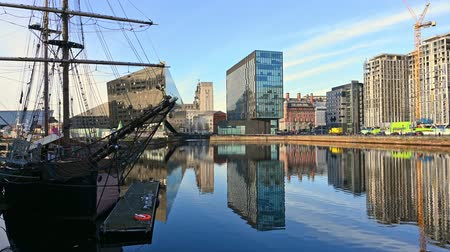 enlatamento : Tall Ship and modern office buildings surrounding Canning Dock redevelopment in Liverpool. Beautiful reflections in the water on a sunny day.