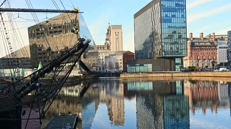 enlatamento : Zoom out from modern office buildings surrounding Canning Dock redevelopment in Liverpool to reveal reflections in the water and a tall ship moored at the side. Vídeos