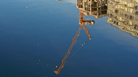 enlatamento : A yellow construction crane and office buildings reflected in deep blue water on a sunny day. Vídeos