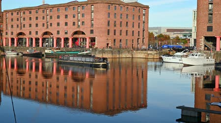victorian : UK, LIVERPOOL - NOVEMBER 10, 2019: Zoom out from a restaurant canal boat maneuvering in the Albert Dock in Liverpool