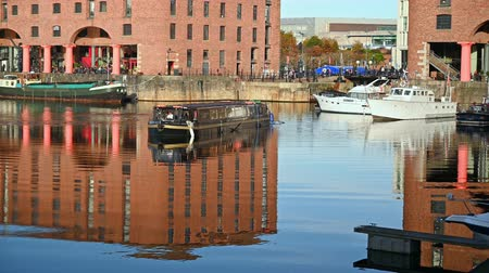 viktoriánus : UK, LIVERPOOL - NOVEMBER 10, 2019: A restaurant canal boat maneuvering in the Albert Dock in Liverpool