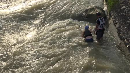 BRATISLAVA, SLOVAKIA - CIRCA  AUGUST, 2017: Three kids wearing canoeing equipment playing around in moving water
