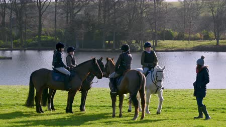 mounted : Aske Hall, Richmond, North Yorkshire, UK - February 08, 2020: Four kids on horse back waiting in front of a lake for a fox hunt to start