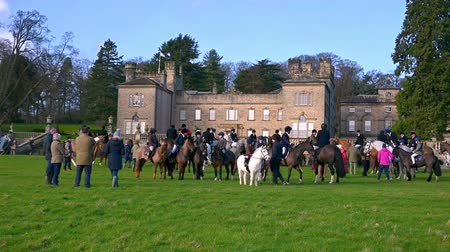 mounted : Aske Hall, Richmond, North Yorkshire, UK - February 08, 2020: Wide shot of horse riders gathered in front of Aske Hall ready for the start of a fox hunt