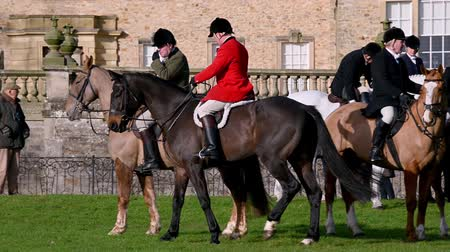 Aske Hall, Richmond, North Yorkshire, UK - February 08, 2020: Horse riding hunt official wearing red coat meeting with members of the field in front of the traditional Georgian country house, waiting for the fox hunt to begin