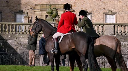 Aske Hall, Richmond, North Yorkshire, UK - February 08, 2020: Two horse mounted members of a fox hunt in front of a traditional Georgian country house and waiting for the hunt to begin. One is an official of the hunt and wearing the traditional red coat